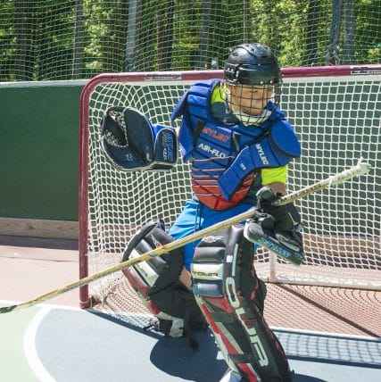 boy in hockey goalie padding in front of a goal