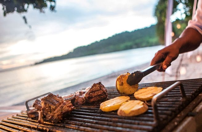 a hand flipping pineapple over on a grill in front of a lake
