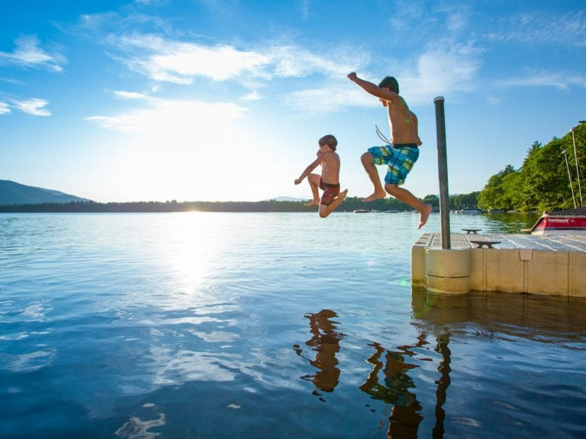 two boys jumping in a lake as the sun's reflection bounces off the water