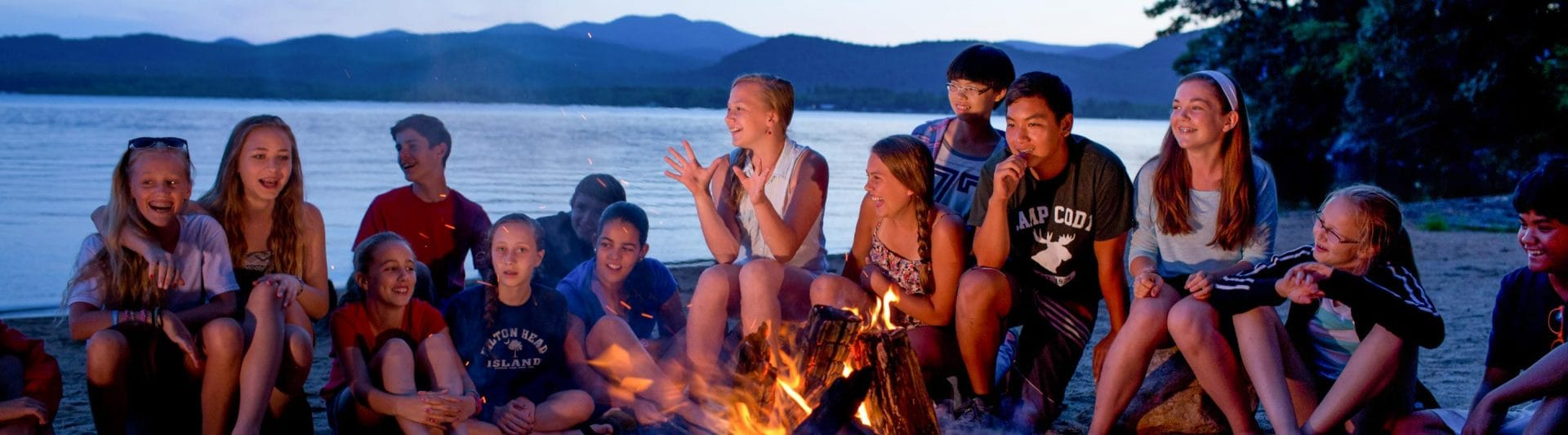 campers smiling around a campfire