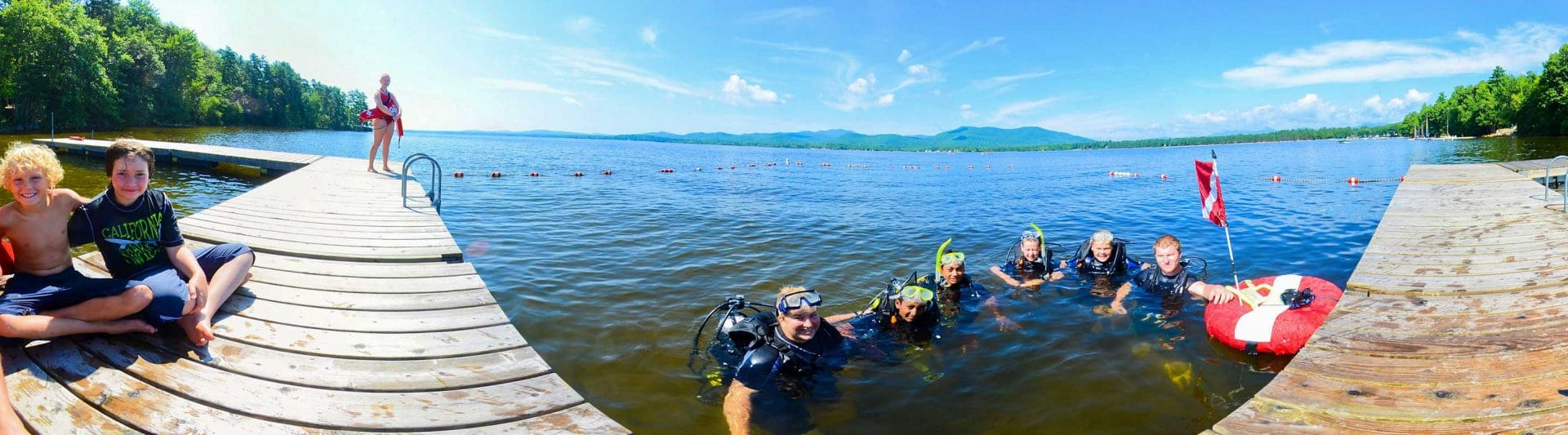group of young campers practicing scuba diving at the lake