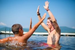 counselor with raised hands while in the lake with two boys