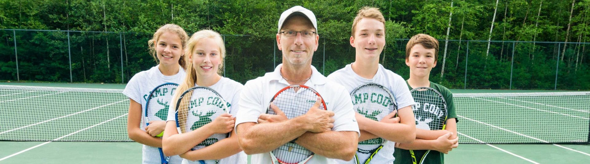 tennis coach and four players flanking him hugging their tennis rackets to their chests