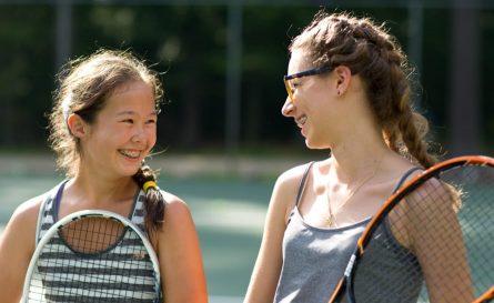 teenage girls playing tennis